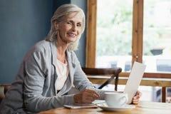 Портрет усмехаясь женщины используя портативный компьютер пока сидящ на таблице Стоковое Изображение RF