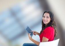 Портрет усмехаясь женщины используя цифровую таблетку против запачканной предпосылки Стоковые Изображения RF