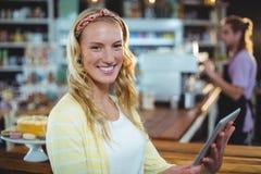 Портрет усмехаясь женщины используя цифровую таблетку Стоковые Изображения