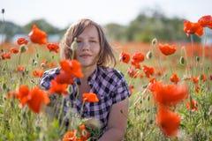 Портрет усмехаясь женщины на поле мака Стоковые Фото