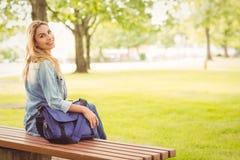 Портрет усмехаясь женщины на скамейке в парке Стоковые Изображения RF