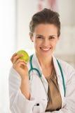 Портрет усмехаясь женщины доктора с яблоком Стоковые Изображения RF