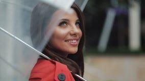 Портрет усмехаясь женщины под зонтиком в городе смотря выглядящ косой Она стоя на улице около дела видеоматериал