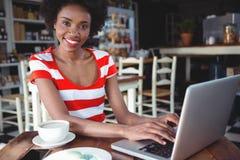 Портрет усмехаясь женщины работая на компьтер-книжке Стоковое Изображение RF