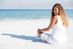 Портрет усмехаясь женщины сидя на пляже Стоковое фото RF