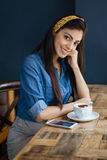 Портрет усмехаясь женщины сидя на таблице Стоковая Фотография RF