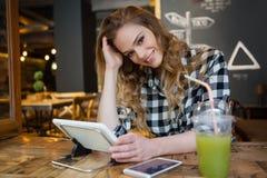 Портрет усмехаясь женщины сидя на таблице Стоковое Изображение