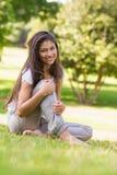 Портрет усмехаясь женщины сидя на траве в парке Стоковое Изображение RF