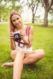 Портрет усмехаясь женщины сидя на траве Стоковые Изображения RF