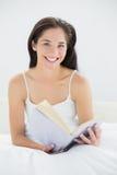Портрет усмехаясь женщины с книгой в кровати Стоковое фото RF