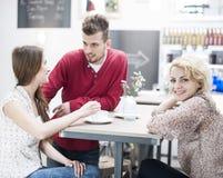 Портрет усмехаясь женщины с другом на таблице кафа Стоковые Фотографии RF