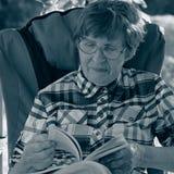 Портрет усмехаясь женщины с стеклами и листая книгой Стоковые Фото