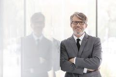 Портрет усмехаясь зрелого бизнесмена с оружиями пересек полагаться на стене на офис стоковое фото rf