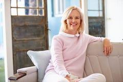 Портрет усмехаясь зрелой женщины сидя на софе дома Стоковые Фотографии RF