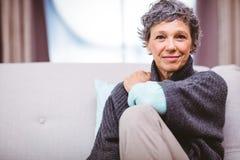 Портрет усмехаясь зрелой женщины сидя на софе Стоковые Изображения RF