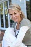 Портрет усмехаясь зрелой женщины сидя outdoors Стоковое Фото