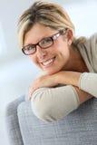 Портрет усмехаясь зрелой склонности женщины на софе Стоковая Фотография