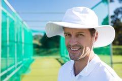 Портрет усмехаясь игрока в крикет стоя на поле стоковая фотография