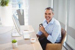 Портрет усмехаясь исполнительной власти сидя на столе Стоковые Фото