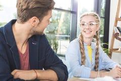 портрет усмехаясь коллег дела имея переговор пока сидящ на таблице стоковая фотография