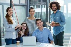 Портрет усмехаясь команды дела обсуждая над компьтер-книжкой в встрече Стоковое Изображение