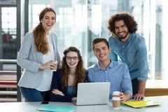 Портрет усмехаясь команды дела работая на компьтер-книжке в встрече Стоковая Фотография