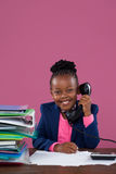 Портрет усмехаясь коммерсантки говоря на телефоне пока делающ обработку документов Стоковое Фото