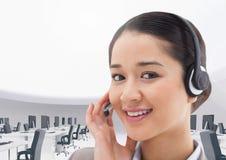 Портрет усмехаясь коммерсантки говоря на шлемофоне в офисе Стоковое Фото