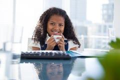 Портрет усмехаясь коммерсантки держа кофейную чашку на столе Стоковые Фотографии RF
