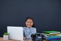 Портрет усмехаясь коммерсантки используя компьтер-книжку против черной предпосылки стоковая фотография