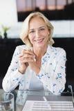 Портрет усмехаясь коммерсантки сидя на столе Стоковые Фото