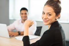 Портрет усмехаясь коммерсантки сидя на таблице Стоковое Фото