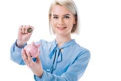 портрет усмехаясь коммерсантки с копилкой и монетки в руках Стоковая Фотография