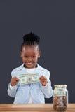 Портрет усмехаясь коммерсантки с опарником на столе показывая бумажные деньги Стоковая Фотография