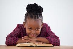 Портрет усмехаясь коммерсантки с склонностью книги на столе Стоковая Фотография