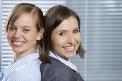 Портрет усмехаясь коммерсанток стоя спина к спине в офисе Стоковое Изображение