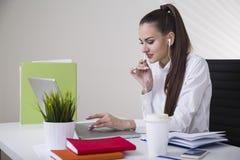 Портрет усмехаясь коричневой с волосами коммерсантки в белой блузке сидя на ее таблице в офисе Стоковая Фотография RF