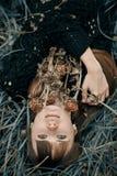 Портрет усмехаясь красивой девушки лежа на зеленой траве Усмехаясь маленькая девочка лежа на цветках объятия крупного плана зелен Стоковая Фотография RF