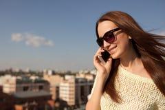 Портрет усмехаясь красивой женщины говоря на телефоне стоковое фото