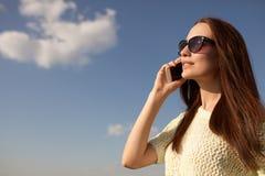 Портрет усмехаясь красивой женщины говоря на телефоне стоковая фотография
