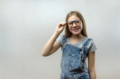 Портрет усмехаясь красивой маленькой девочки со стеклами Умный ребенок nerdy стоковые фото