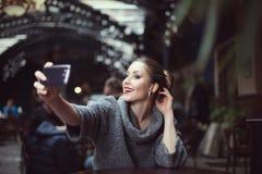 Портрет усмехаясь красивой молодой женщины делая фото selfie с ее smartphone Стоковое фото RF