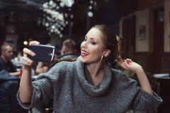Портрет усмехаясь красивой молодой женщины делая фото selfie с ее smartphone Стоковые Фотографии RF