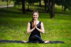 Портрет усмехаясь красивой sporty молодой женщины разрабатывая в переулке парка, стоя при ладони касаясь в Namaste Стоковое Изображение RF