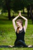 Портрет усмехаясь красивой sporty молодой женщины разрабатывая в переулке парка, стоя при ладони касаясь в Namaste Стоковые Фото