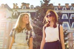 Портрет 2 усмехаясь красивых девушек, подростков 13, 14 лет, конца-вверх, девушек говоря смеяться и идти в город лета стоковое изображение rf