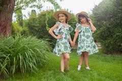Портрет усмехаясь красивых девушек с шляпами против зеленой травы на парке лета Стоковая Фотография