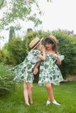 Портрет усмехаясь красивых девушек с шляпами против зеленой травы на парке лета Стоковые Изображения