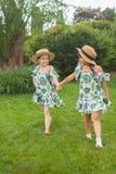 Портрет усмехаясь красивых девушек с шляпами против зеленой травы на парке лета Стоковые Фото