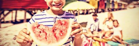 Портрет усмехаясь мальчика держа арбуз с семьей в предпосылке стоковое изображение rf